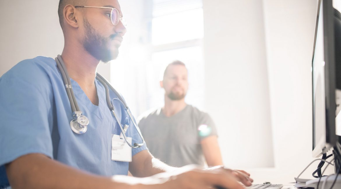 Serious doctor filling in electronic document with data of patient by computer